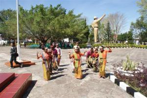 These children greeted us with a traditional dance, note the military statue behind them