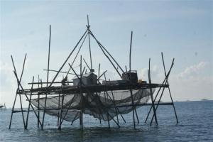 Fishing structure with fisherman rigging his nets